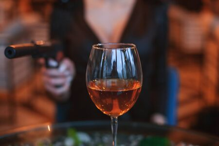 Glass of alcohol close up. Behind him the silhouette of a woman with a gun.