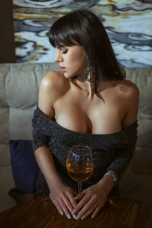 Attractive young woman holds a glass of wine in her hands and looks away.
