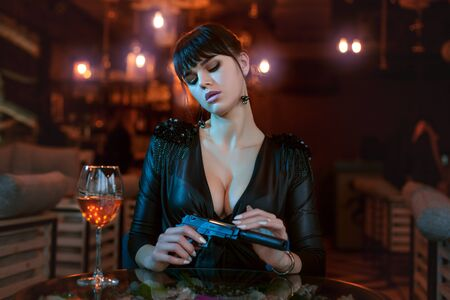 Sexy young woman sits at a table and holds a gun in her hands.