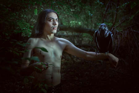 A creepy man with a raven on his hand looks like a demon.