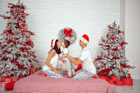 The child kisses mom on Christmas. Family in the bedroom.