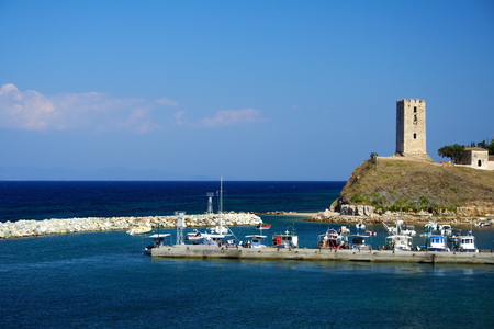 freedom tower: colorful boats and an ancient tower in Greece Stock Photo