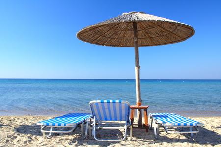 beach umbrella and three chairs in Greece Stock Photo