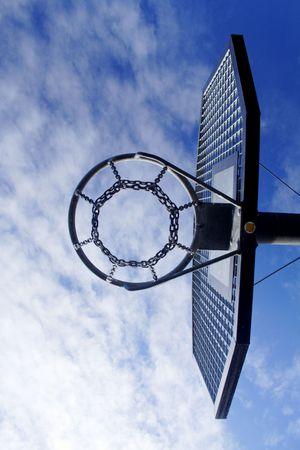 Basketball hoop and backboard set against a blue sky