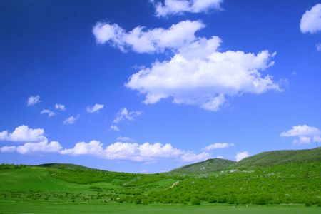 Green field and hills with blue sky and clouds photo