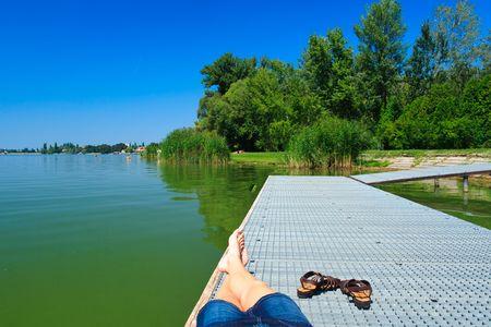 legs over the green lake in Tata Reklamní fotografie