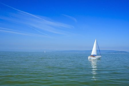White sailboat with blue background in lake Balaton photo