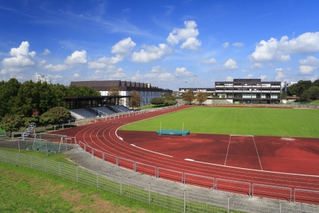 Red athletics track with green field photo