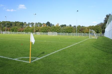 kickball: Green empty footballfield in sommer with white flag