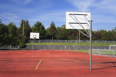Red, empty outdoor basketball field with trees