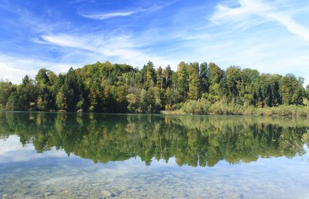 green lake with colorful wood and blue sky in autumn