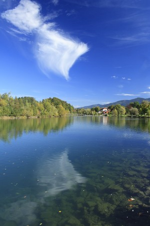 river in autumn with colorful trees and blue sky