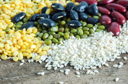 white sesame seeds: bean and white sesame seeds pile on wood close up Stock Photo