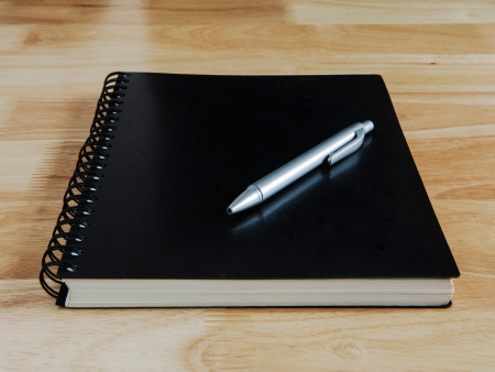 notebook and pen on wooden desk photo