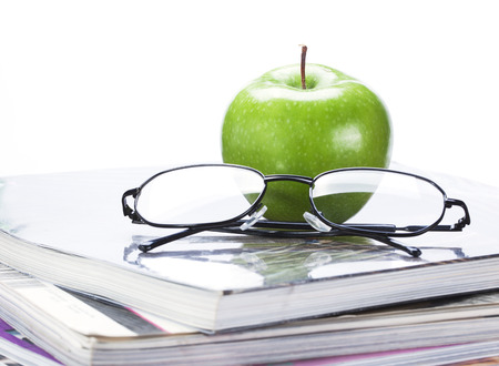 green apple and glasses on magazine and  book stack close up photo