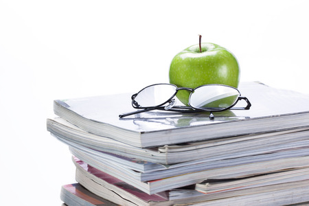 green apple and glasses on magazine and  book stack photo