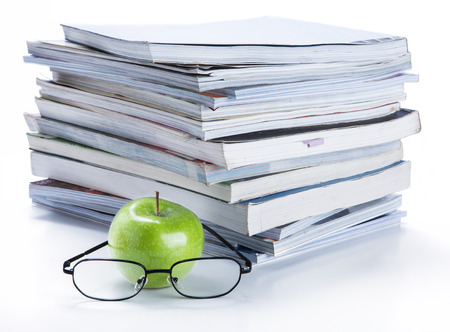 green apple and glasses with magazine and  book stack photo