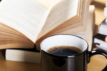 evening newspaper: coffee in black cup and book pile