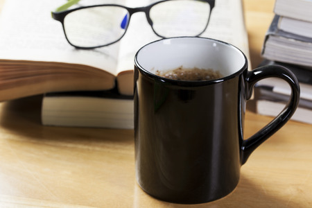 evening newspaper: black coffee cup and book pile