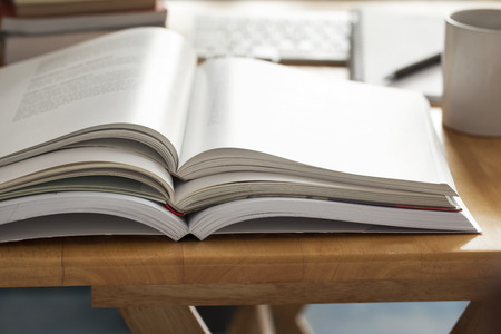 evening newspaper: opened book pile put on table Stock Photo