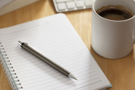 evening newspaper: pen with notebook on working table Stock Photo