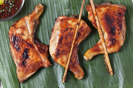brunt: thai grilled chicken with spicy sauce on banana leaf