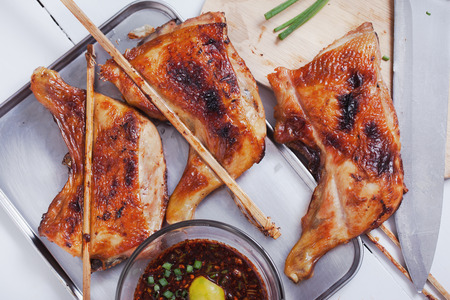 brunt: thai grilled chicken with spicy sauce on tray Stock Photo