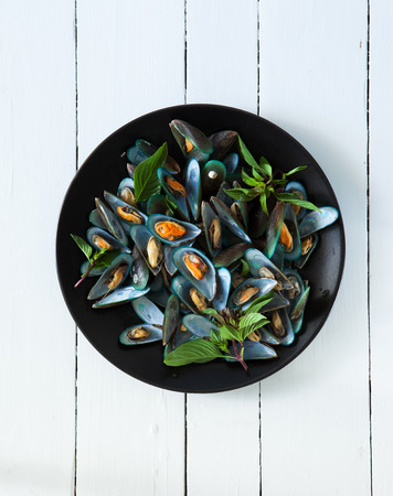 scald: scald mussel with thai sweet basil in black plate Stock Photo