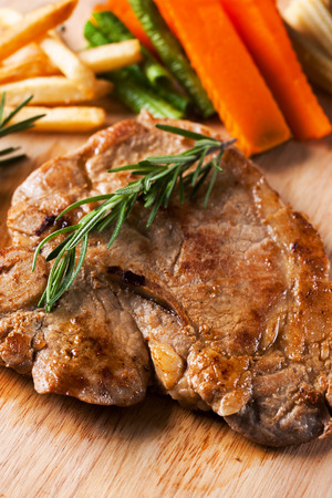 grilled pork chop: grilled pork chop with vegetable and french fries on wooden board