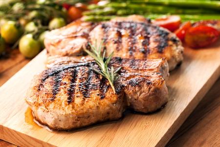 grilled pork chop with vegetable on wooden board Banco de Imagens - 48533356