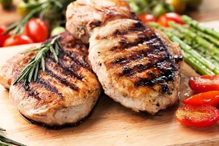 meat on grill: grilled pork chop with vegetable on wooden board