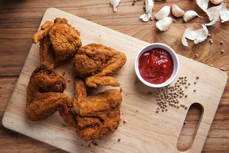 fried chicken wings with tomato sauce on wooden board Stock Photo
