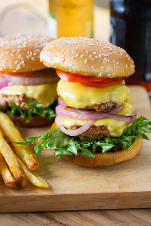 double cheese hamburger and french fries on wooden board Stock Photo