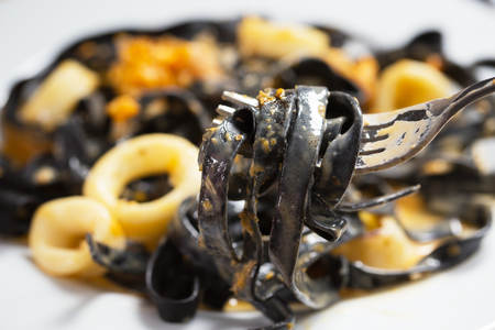 ink squid pasta with cuttlefish on fork