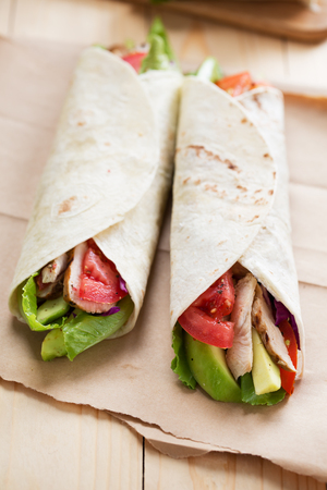 tortilla wrap with grilled chicken,avocado and vegetable on paper