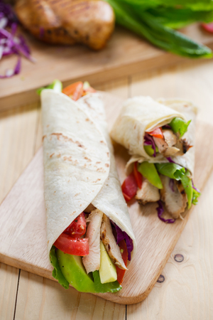 tortilla wrap with grilled chicken,avocado,tomato and lettuce on wooden board