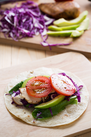 grilled chicken,avocado,tomato and lettuce on tortilla on wooden board