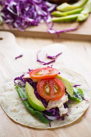 grilled chicken,avocado,tomato,purple cauliflower and lettuce on tortilla