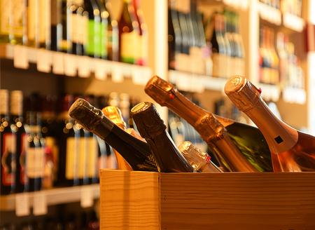 Wine bottles on wooden shelf in wine store