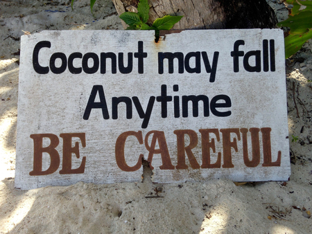 poser: Warning sign under coconut trees Stock Photo