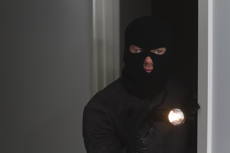 Burglar holding flash light photo