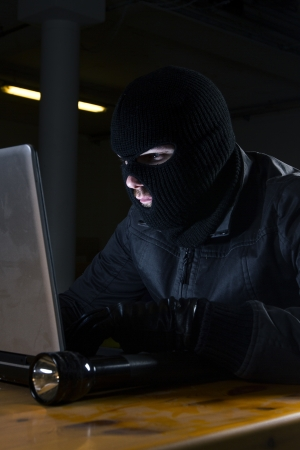 masked hacker sitting behind compuiter photo