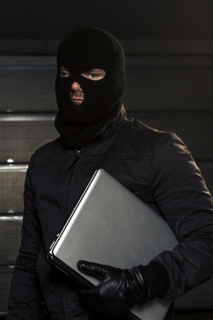 masked hacker holding computer photo