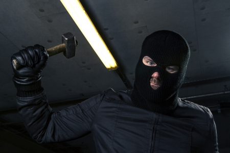 masked criminal with hammer photo