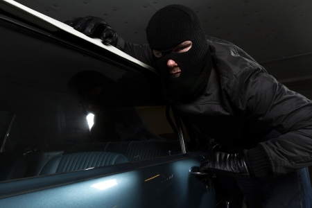 man trying to steal blue car photo
