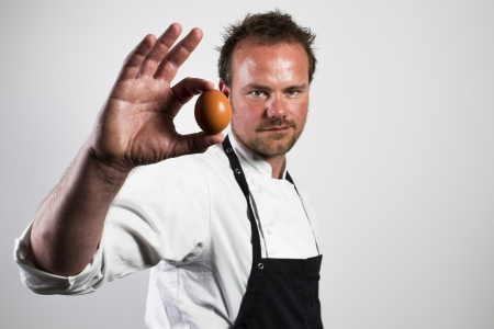 Jonge chef-kok die een ei Stockfoto