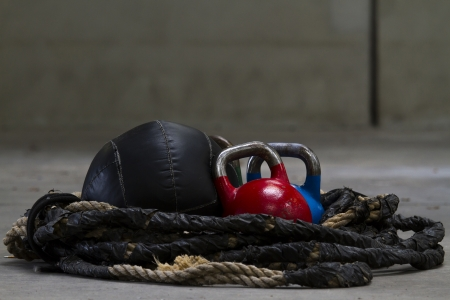 Kettle bells, rope and a medicine ball used for crossfit Imagens