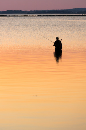 Man standing in water fishing photo