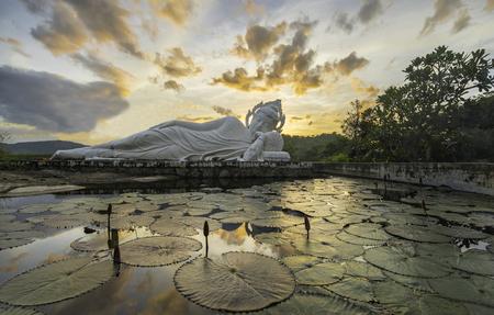 buddhism prayer belief: Sleeping Buddha and belfry on sunset at Hua-Hin,Thailand