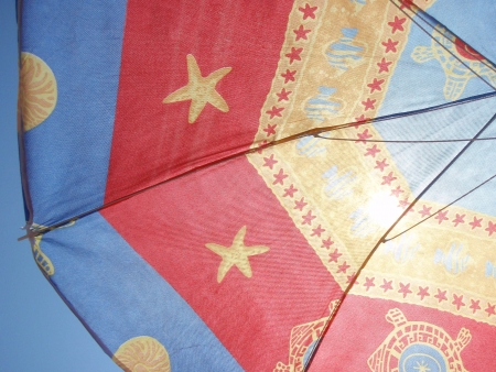 Red, blue and yellow parasol, blue sky in background